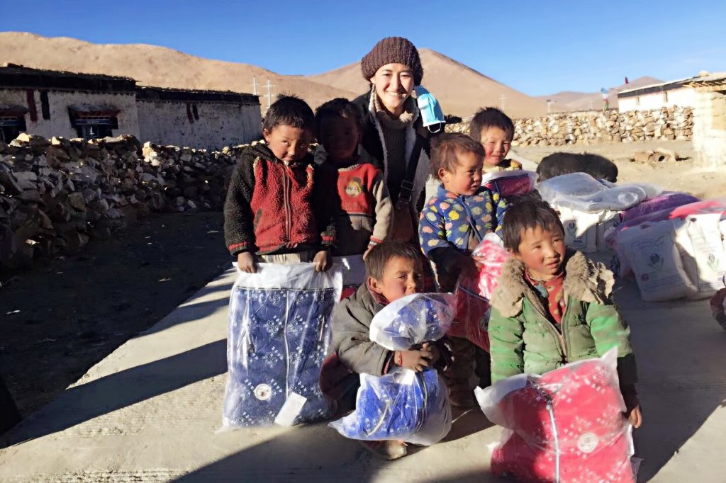distributing warm winter clothes to Tibetan school children by Tibet Universal Travel