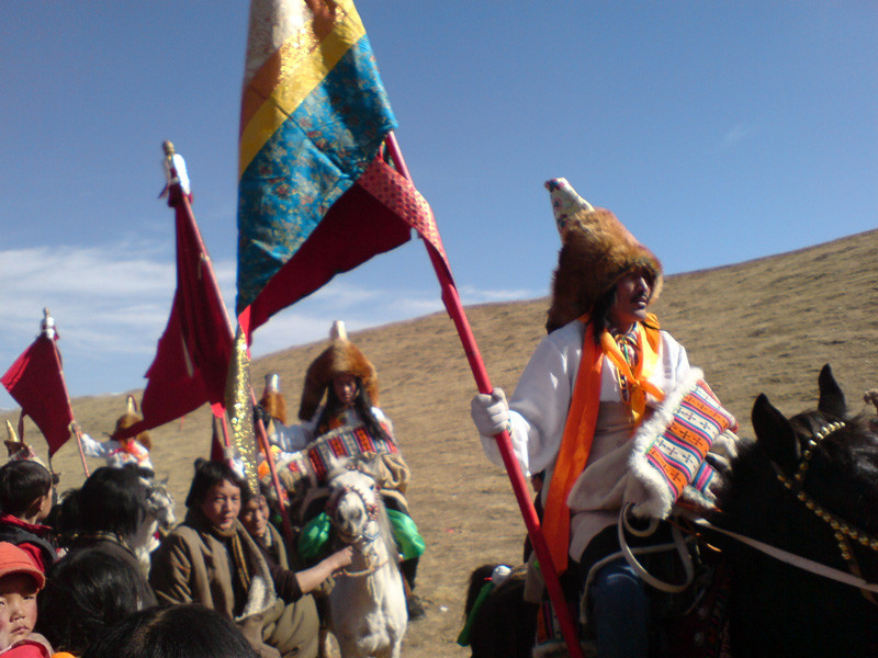 Riders with banners during horse festival Tibet